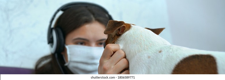 teenage young girl wearing protective facemask and headphones have fun with your pet dog on bed at home inside