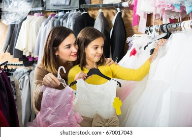 Teenage-girl with mother are acquiring fashionable dress in children's clothing store.