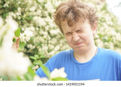 Teenager with allergies standing in a blue t-shirt among the Jasmine bushes and suffers from bad health