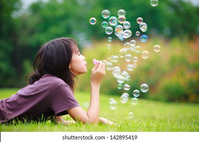 Teenager asian girl with soap bubbles in the park
