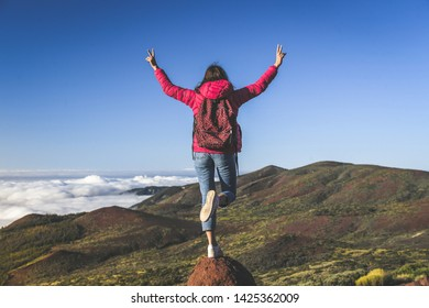 Teenager with backpack and raised hands standing on a mountain cliffs edge with gorgeous view to forest sea and clouds Volcano Teide Tenerife Spain Adventure freedom tourism carefree and youth concept