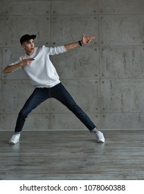 Teenager in baseball cap and sneakers, jeans and white sweater dances hip-hop. Dynamics of modern dance movement. Youth fashion.
