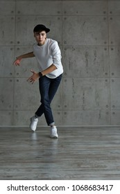 Teenager in baseball cap and white sneakers, jeans and white sweater dances hip-hop. Dynamics of modern dance movement. Youth fashion.