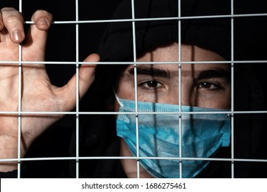 a teenager with black eyebrows in a black hood and an individual mask stands behind bars, his hand on the bars. Focus on the grill. Syrian refugee problem in Europe