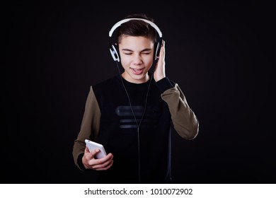 teenager in a black sweatshirt in white headphones and with a phone in his hands, sing along, listens to music on a black background
