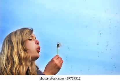 Teenager blowing dandelion