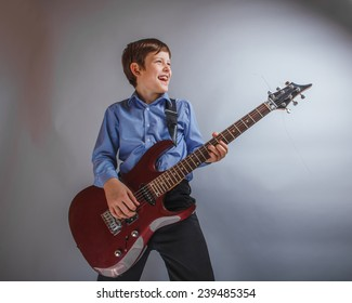 teenager boy of 10 years of European appearance smiles plays guitar on a gray background
