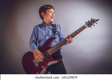 teenager boy of 10 years of European appearance smiles plays guitar on a gray background cross process