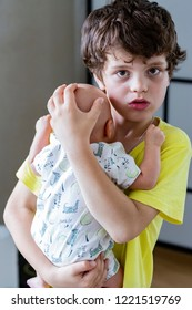 A teenager boy of 10 years old is holding the baby boy in his hands and looking concerned and disquieted. Older brother takes care of younger. Colic in a newborn baby. New family member.