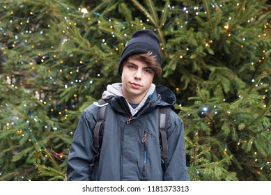 Teenager boy with anorak and a black cap looking at camera with a Christmas tree in the background