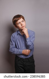 teenager boy brown hair of European appearance holds a hand under his chin deep in thought on a gray background