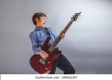 teenager boy brown hair European appearance playing guitar, happy on a gray background