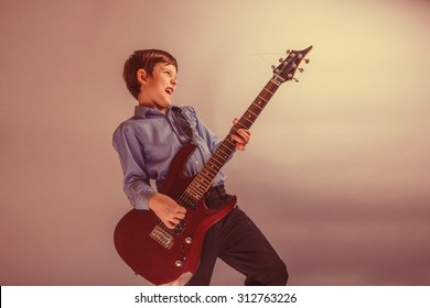 teenager boy brown hair European appearance playing guitar, happy on a gray background retro