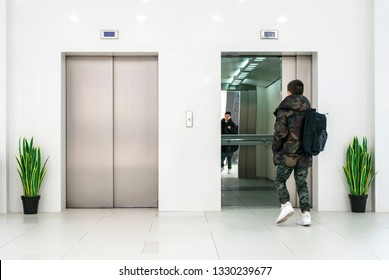 Teenager boy with casual clothes and white sneakers enters in elevator. White contemporary building interior. Flowers in pots and white wall. Metallic elevator doors.
