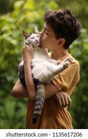 teenager boy with cat kiss hug on green summer grass close up photo