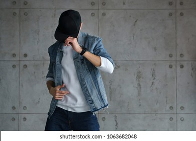 Teenager boy denim jacket and white sweater dancing hip-hop with baseball cap. Dynamics and plastic movement of modern dance. Youth fashion. Man is unrecognizable