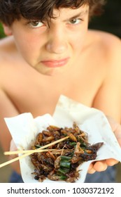 teenager boy with disgust grimace hold unusial strange thai food roasted insects silkworm and grasshopper on stick close up outdoor portrait