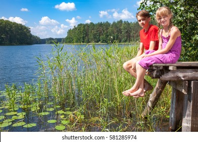 Teenager boy and elementary age girl sitting on a wooden pier by a forest lake enjoying summer day outdoors