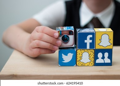 Teenager boy folds cubes with the logo of popular social networks. Instagram. Facebook. Twitter. Snapchat. Like. Icons. Concept. Minsk, Belarus - April, 2017.