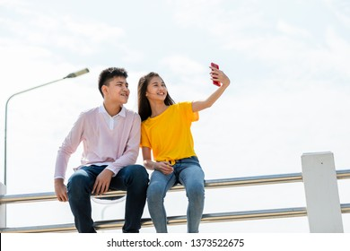 teenager boy and girl asia thailand holding hand selfie and smiling on smartphone technology