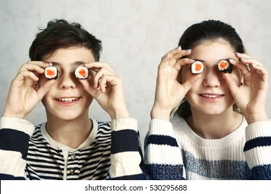 teenager boy and girl with sushi japanese roll eyes smiling close up portrait.