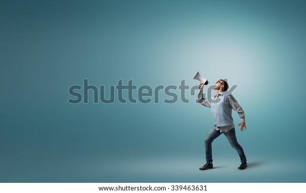 Teenager-Junge in Brillen, der in Megaphon emotional schreiend