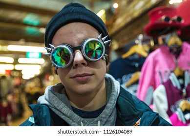 Teenager boy with a Gothic sunglasses with diffracted lens or Kaleidoscope in a fashion shop of Camden Lock Market or Camden Town in London, England, United Kingdom