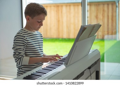 Teenager boy has training course with white e-piano at home