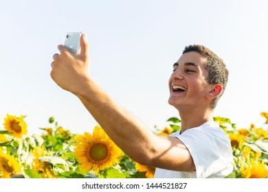 Teenager boy having a selfie in a sunflowers field