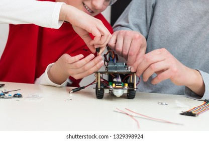 A teenager boy with his dad teacher collects a handmade metal and plastic robot. STEM education for children and teenagers, robotics and electronics. DIY. AI. STEAM.