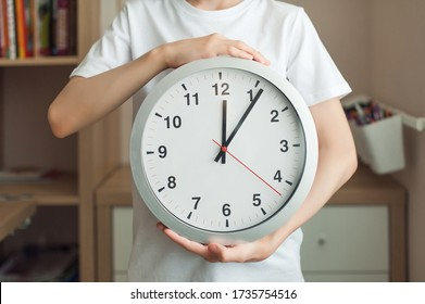 A teenager boy is holding a big clock with big numbers. A child in a white T-shirt, a watch close-up, a person is not visible. Concept mode, schedule, rest.