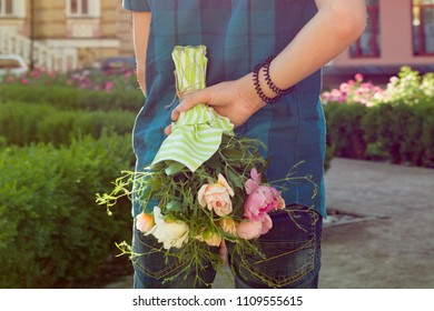 Teenager boy holding bouquet of flowers behind his back. Surprise, gift, present.
