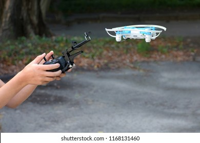 Teenager boy holding copter control panel with flying blue drone on blurred background