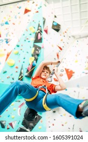 Teenager boy at indoor climbing wall hall. Boy is climbing using an auto belay system and climbing harness. Active teenager time spending concept image.