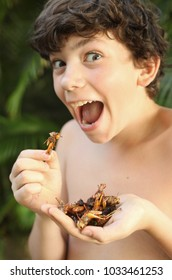 teenager boy with joy grimace hold unusial strange thai food roasted insects silkworm and grasshopper on stick close up outdoor portrait