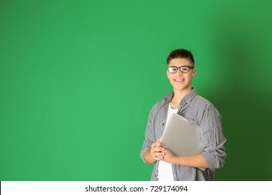Teenager boy with laptop on color background