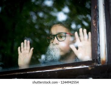Teenager boy looking out at windows raining drops