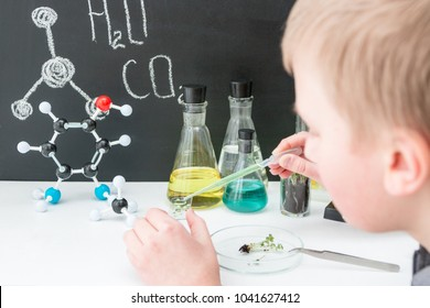 Teenager boy makes test at the lab. STEM education. Robot in the class of engineering and chemistry. Modern technologies. Robotics. Black background. Bot. Molecule. Tubes.