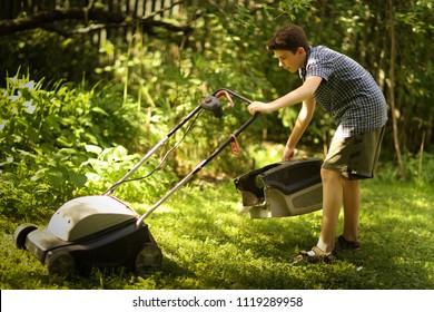 teenager boy mooving lawn in green summer garden