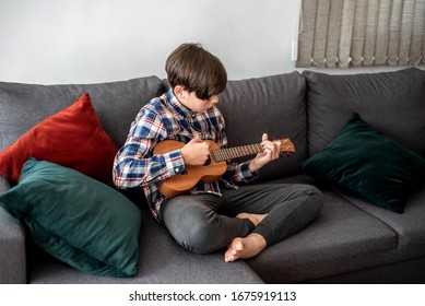 Teenager boy playing his ukulele at home