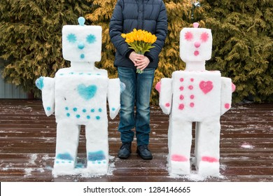 A teenager boy prepared a surprise for his mother on Valentine's Day, Mother's Day, Women's Day on March 8. He blinded robots snowmen in love. Holding a large bouquet of tulips. Concept. Holiday card.