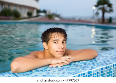 teenager boy relaxing near ledge in pool open-air, looking at camera