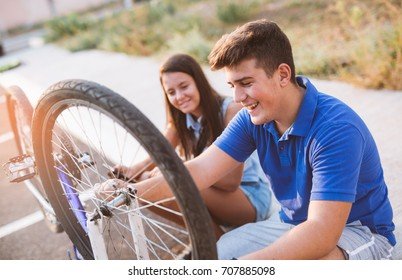 Teenager boy repair tire on bicycle , female friend sitting next to him, summer outdoor photo