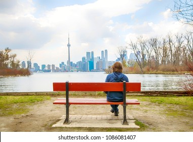Teenager boy sitting on the Bench in the Toronto Islands, City View, Toronto, Ontario, Canada
