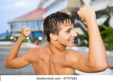 teenager boy standing near hotel on resort in evening, teenager boy with naked torso, shows muscles