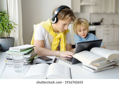 Teenager boy study at home. His younger brother is playing near. Homeschooling. Online education and distance learning for children during lockdown. Friendship of siblings with a big age difference.