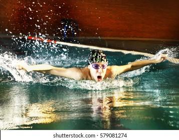 teenager boy swim butterfly style in swimming pool
