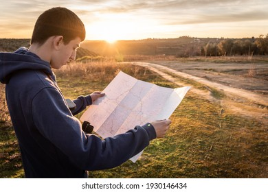 Teenager boy using map in the countryside and enjoying sunset. Selective focus.
