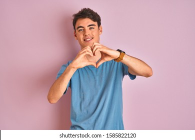 Teenager boy wearing casual t-shirt standing over blue isolated background smiling in love showing heart symbol and shape with hands. Romantic concept.