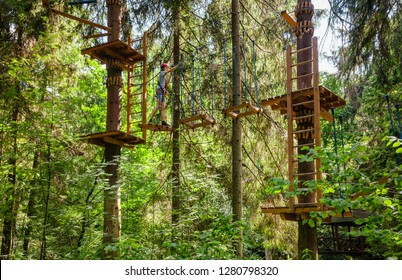 Teenager boy wearing safety harness passing rope bridge obstacle at a ropes course in outdoor treetop adventure park